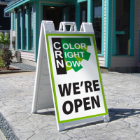 "Sandwich board with Color Right Now logo and ""We're Open"" printed on it."